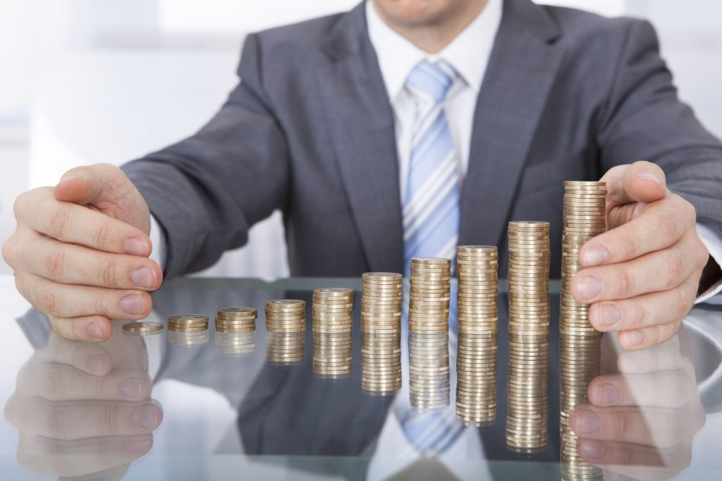 Businessman Protect Stack Of Coins