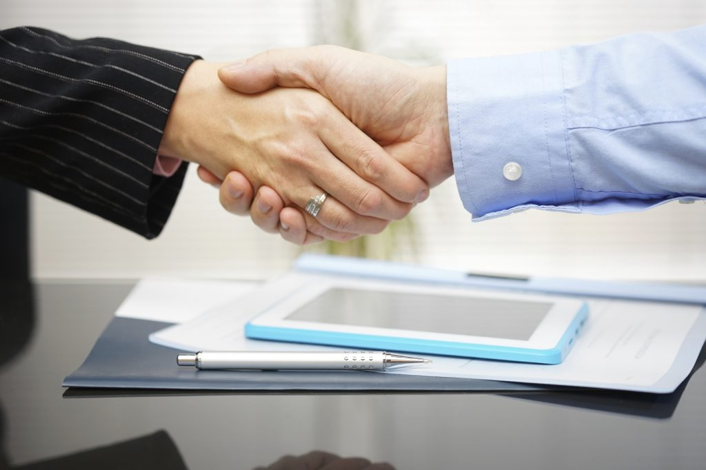 businessman and businesswoman are handshaking over documents and presentation