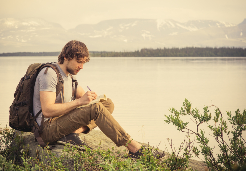Young Man Traveler reading book and writing notes outdoor