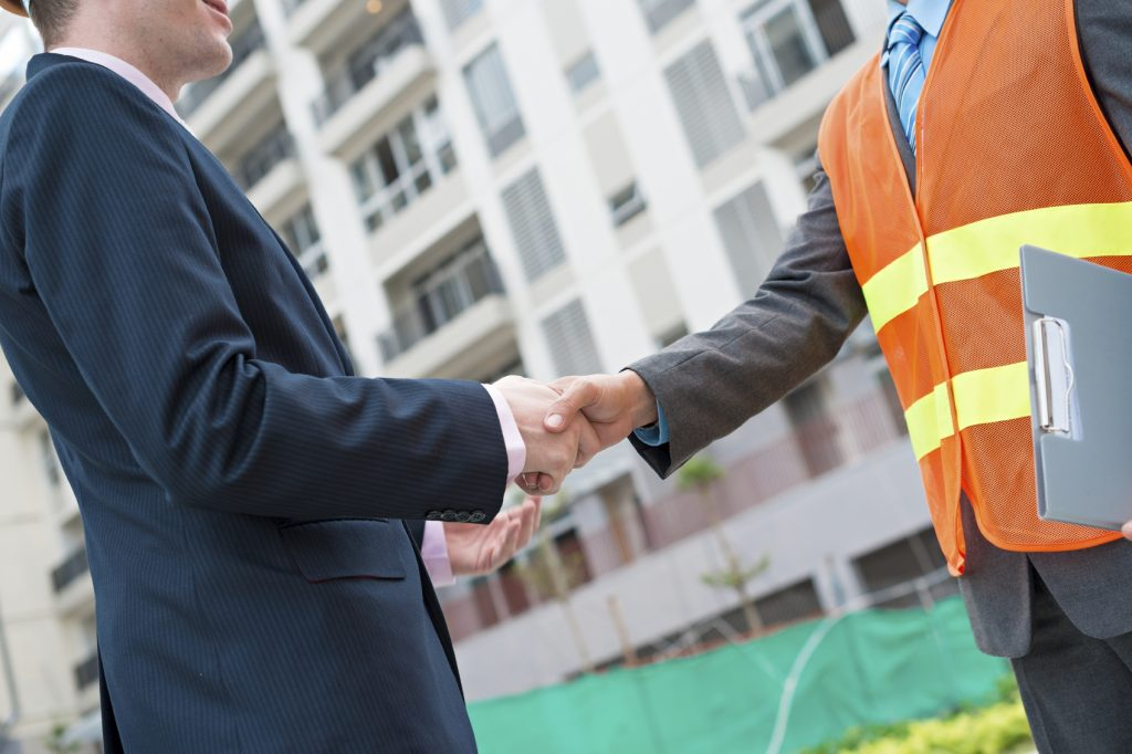 Cropped image of businessman shaking hands with construction worker