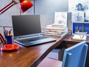 Designer modern home office desk with laptop and equipment
