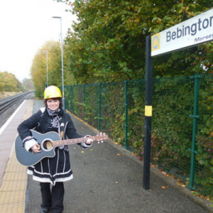 Woman on Platform of Bebington Station, Merseyside, Playing Guitar